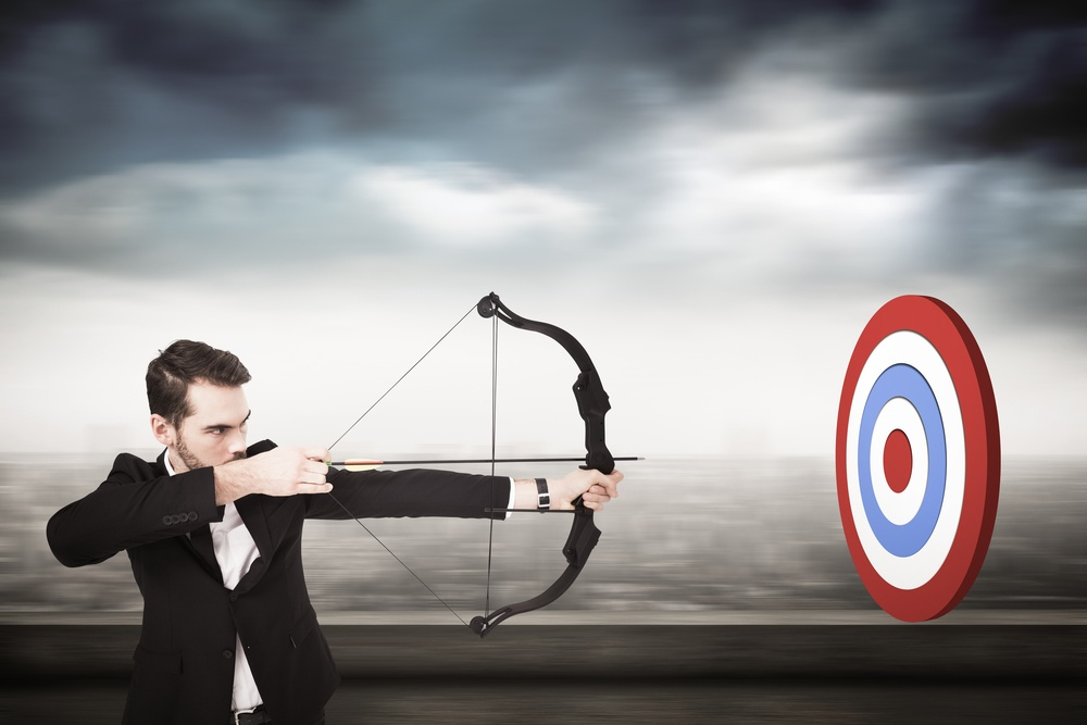 Elegant businessman shooting bow and arrow against cityscape.jpeg