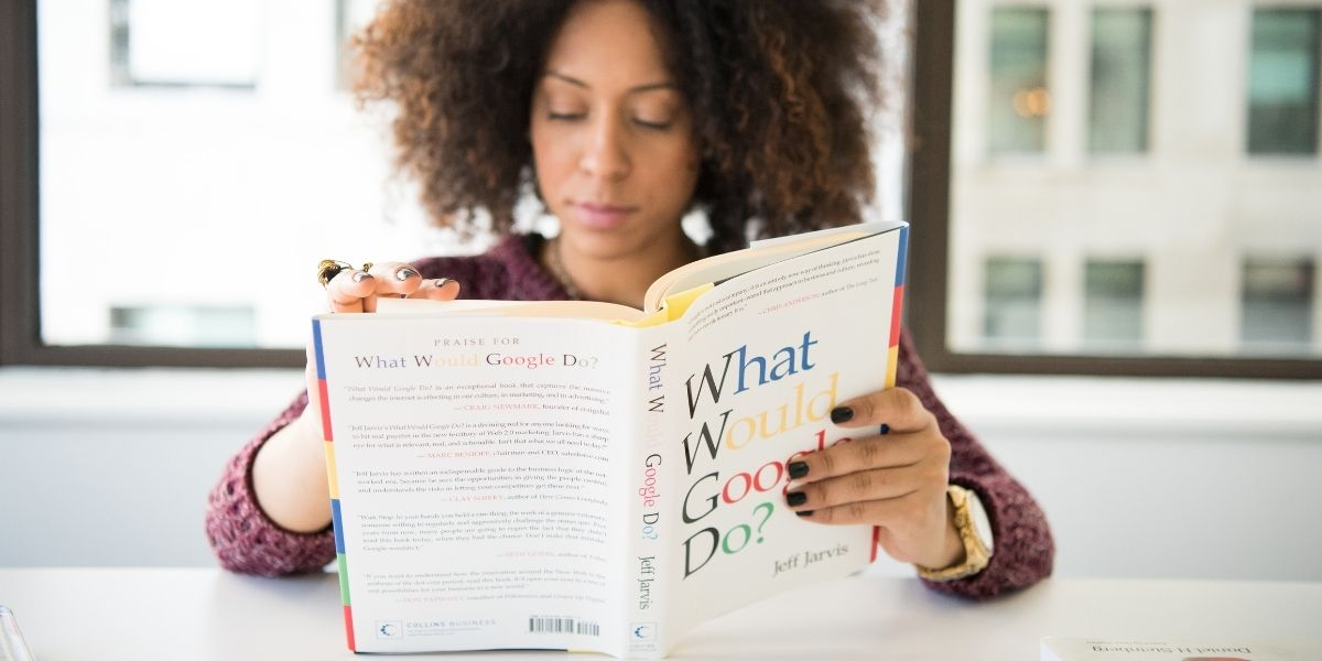 A woman reading a book on Google, signifying a need to research how to overcome SMB digital marketing challenges related to search engine marketing